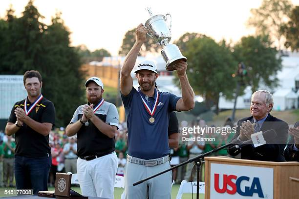 Dustin Johnson of the United States raises the trophy as John Rahm of Spain the leading amateur Shane Lowry of Ireland the runnerup and Jack Nicklaus...