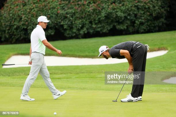 Dustin Johnson of the United States reacts after missing his par putt on the 15th green as Brooks Koepka of the United States looks on during the...