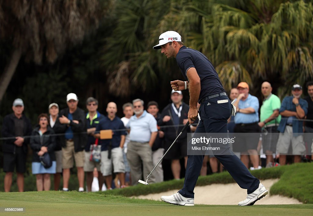 Dustin Johnson of the United States reacts after putting out on the eleventh hole green during the final round of the World Golf...