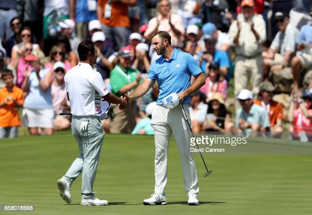 Dustin Johnson of the United States shakes hands with his opponent Hideto Tanihara of Japan on the 18th green Johnson won by 1 hole during the...