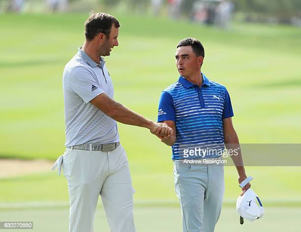 Dustin Johnson of the United States shakes hands with Rickie Fowler on the 18th green during the third round of the Abu Dhabi HSBC Championship at...