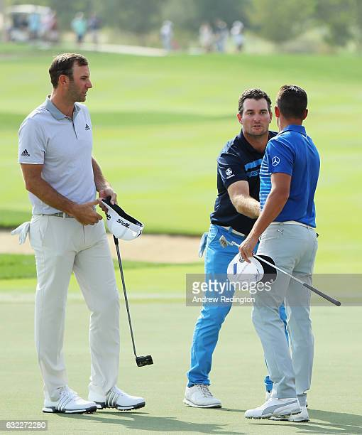 Dustin Johnson of the United States shakes hands with Ryan Fox of New Zealand and Rickie Fowler on the 18th green during the third round of the Abu...