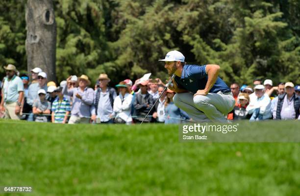 Dustin Johnson of the United States studies his putt on the third hole during the final round of the World Golf ChampionshipsMexico Championship at...