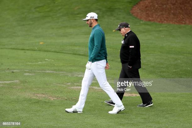 Dustin Johnson of the United States walks with coach Butch Harmon on the range prior to his tee time for the first round of the 2017 Masters...
