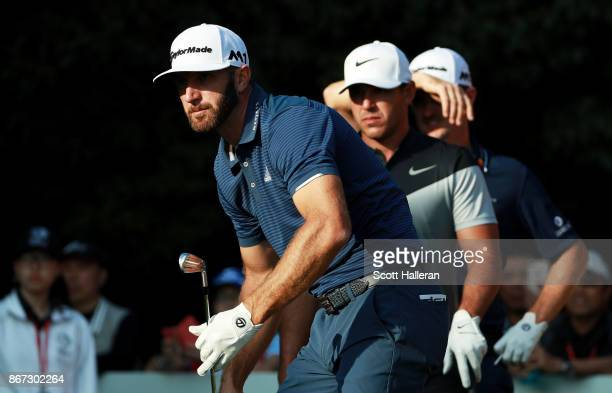 Dustin Johnson of the United States watches his shot from the 16th tee as Brooks Koepka of the United States and Justin Rose of England look on...
