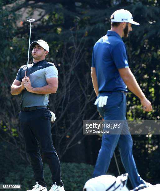 Dustin Johnson of the US walks past as Brooks Koepka of the US reacts to a putt during the third round of the WGCHSBC Champions at the Sheshan...