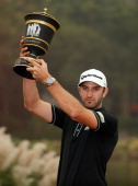 Dustin Johnson of the USA poses with the trophy after his threestroke victory at the WGCHSBC Champions at the Sheshan International Golf Club on...