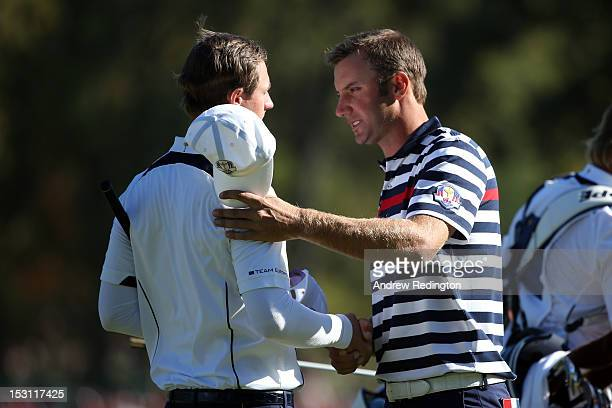Dustin Johnson of the USA shakes hands with Nicolas Colsaerts on the 16th green after defeating Nicolas Colsaerts of Europe 32 during the Singles...