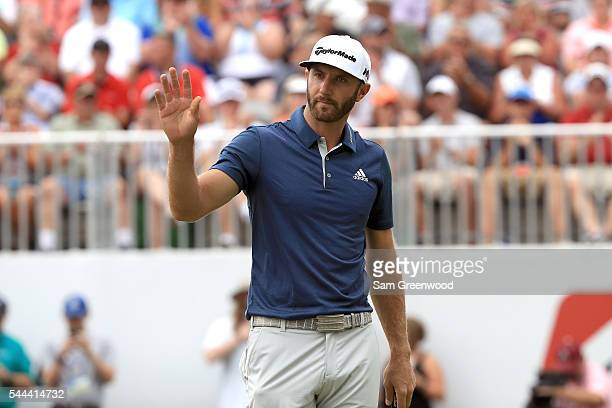 Dustin Johnson reacts on the 18th green after a putt during the final round of the World Golf Championships Bridgestone Invitational at Firestone...