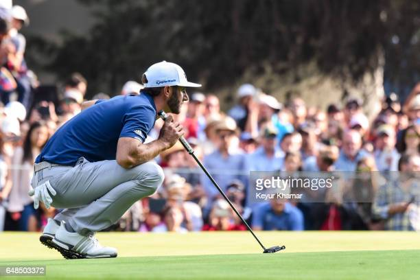 Dustin Johnson reads his putt on the 18th hole green as fans watch during the final round of the World Golf ChampionshipsMexico Championship at Club...