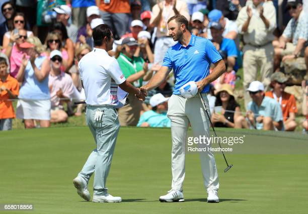 Dustin Johnson shakes hands with Hideto Tanihara of Japan after winning their match 1 up on the 18th hole during the semifinals of the World Golf...