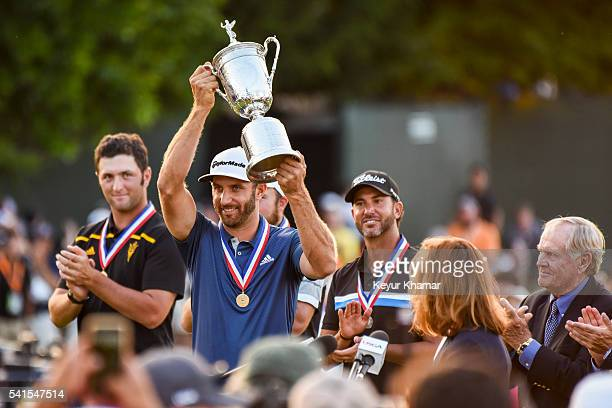 Dustin Johnson smiles as he receives the championship trophy following his three stroke victory in the final round of the US Open at Oakmont Country...