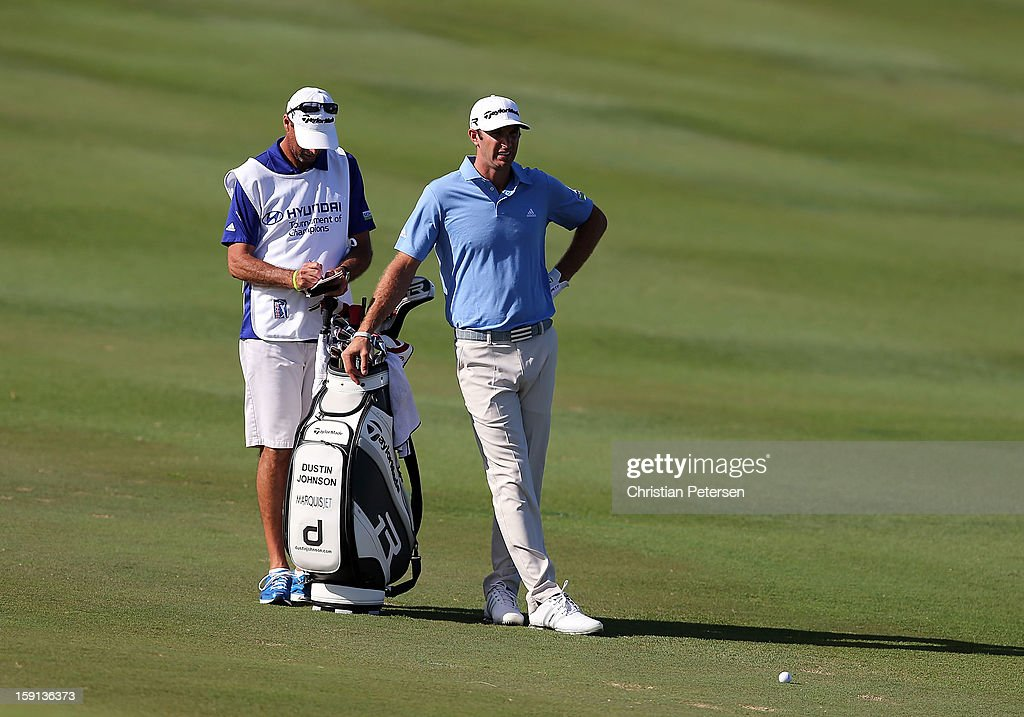 Dustin Johnson stands with his caddie and bag before hitting on the 10th hole fairway during the final round of the Hyundai Tournament of Champions at the Plantation Course on January 8, 2013 in Kapalua, Hawaii.