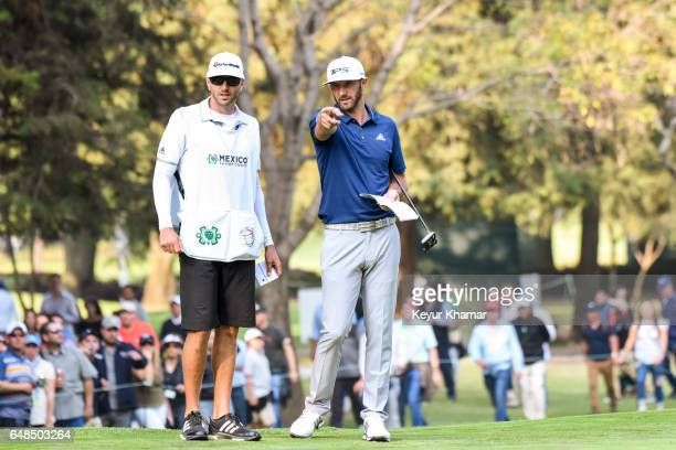 Dustin Johnson talks to his caddie Austin Johnson on the 16th hole green during the final round of the World Golf ChampionshipsMexico Championship at...
