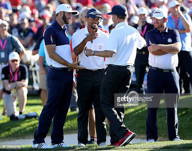 Dustin Johnson vicecaptain Tiger Woods and captain Davis Love III of the United States celebrate after winning the Ryder Cup during singles matches...
