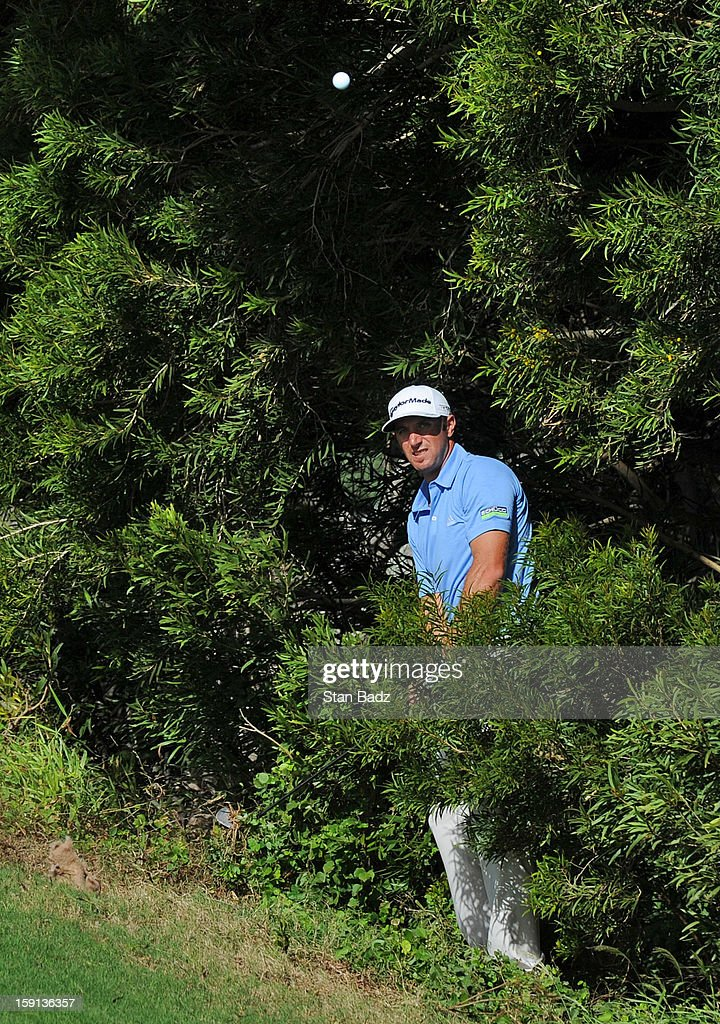 Dustin Johnson watches his chip shot from the trees on the 13 hole during the final round of the Hyundai Tournament of Champions at Plantation Course at Kapalua on January 8, 2013 in Kapalua, Maui, Hawaii.