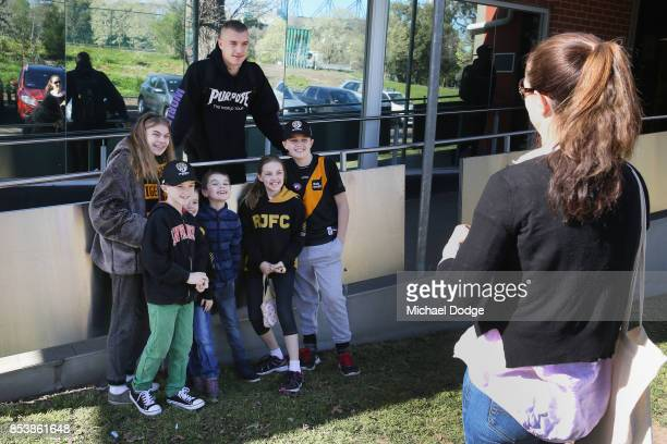 Dustin Martin a winner of the Brownlow medal last night poses with young Tigers fans ahead of the Richmond Tigers AFL training session at Punt Road...