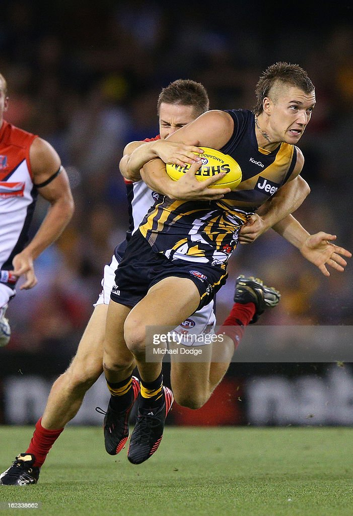 Dustin Martin of the Richmond Tigers gets tackled by Jack Grimes of the Melbourne Demons during the round one AFL NAB Cup match between the Richmond Tigers and the Melbourne Demons at Etihad Stadium on February 22, 2013 in Melbourne, Australia.