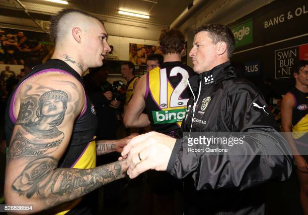 Dustin Martin of the Tigers and Tigers head Damien Hardwick celebrate after the Tigers defeated the Hawks during the round 20 AFL match between the...