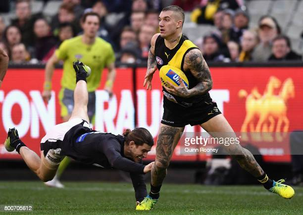 Dustin Martin of the Tigers avoids a tackle by Bryce Gibbs of the Blues during the round 14 AFL match between the Richmond Tigers and the Carlton...