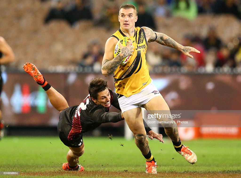 <a gi-track='captionPersonalityLinkClicked' href=/galleries/search?phrase=Dustin+Martin&family=editorial&specificpeople=5404528 ng-click='$event.stopPropagation()'>Dustin Martin</a> of the Tigers beats the tackle of Mark Baguley of the Bombers during the 2016 AFL Round 10 Dreamtime at the G match between the Essendon Bombers and the Richmond Tigers at the Melbourne Cricket Ground on May 28, 2016 in Melbourne, Australia.