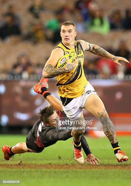 Dustin Martin of the Tigers beats the tackle of Mark Baguley of the Bombers during the 2016 AFL Round 10 Dreamtime at the G match between the...