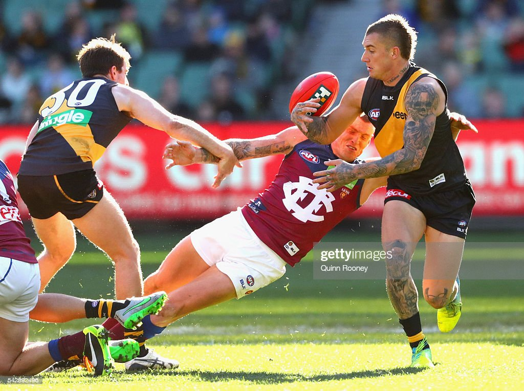 <a gi-track='captionPersonalityLinkClicked' href=/galleries/search?phrase=Dustin+Martin&family=editorial&specificpeople=5404528 ng-click='$event.stopPropagation()'>Dustin Martin</a> of the Tigers breaks free of a tackle by Mitch Robinson of the Lions during the round 14 AFL match between the Richmond Tigers and the Brisbane Lions at Melbourne Cricket Ground on June 25, 2016 in Melbourne, Australia.