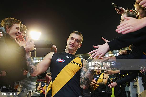 Dustin Martin of the Tigers celebrates the win with fans during the round 20 AFL match between the Richmond Tigers and the Collingwood Magpies at...