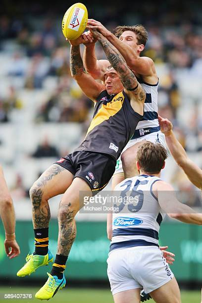 Dustin Martin of the Tigers compete for the ball against Tom Hawkins of the Cats during the round 21 AFL match between the Richmond Tigers and the...
