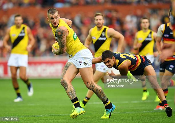 Dustin Martin of the Tigers evades a tackle from Charlie Cameron of the Crows during the round six AFL match between the Adelaide Crows and the...