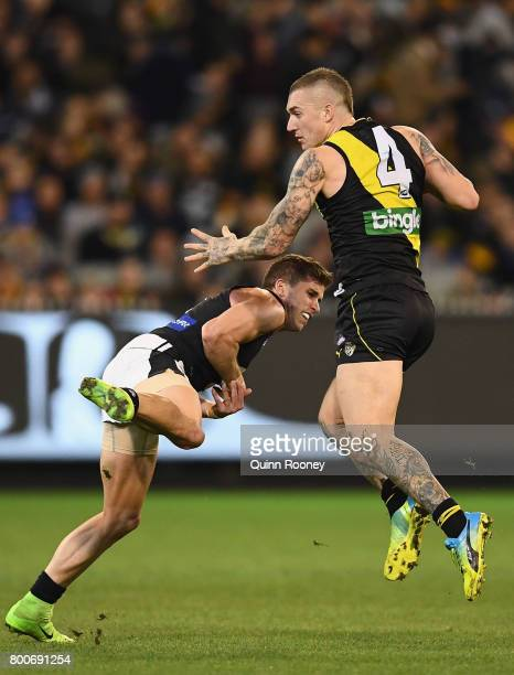 Dustin Martin of the Tigers fends off a tackle by Marc Murphy of the Blues during the round 14 AFL match between the Richmond Tigers and the Carlton...