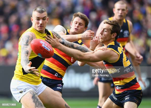 Dustin Martin of the Tigers fends off a tackle by Richard Douglas of the Crows during the 2017 AFL Grand Final match between the Adelaide Crows and...
