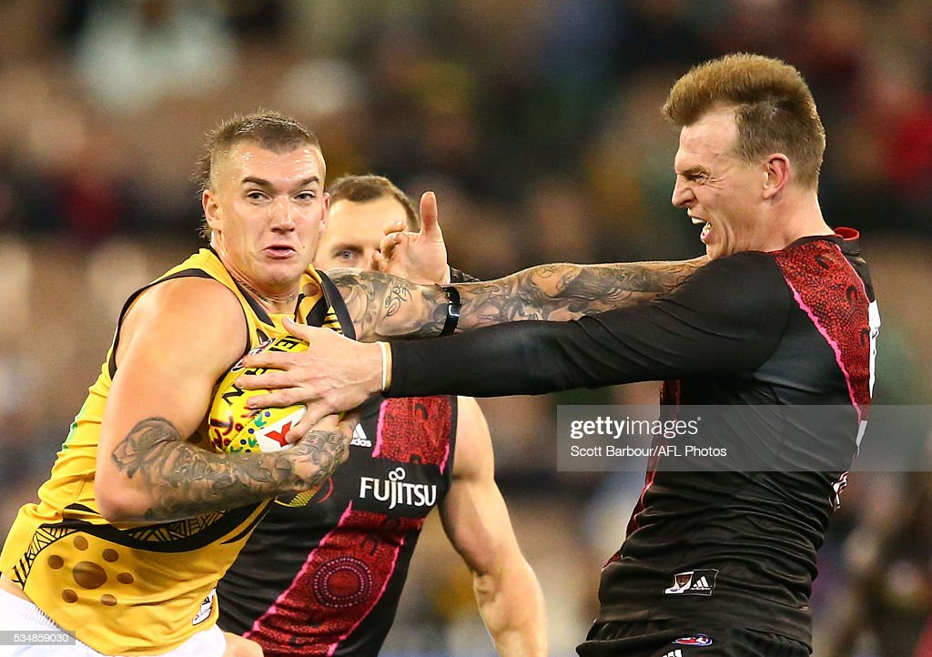 <a gi-track='captionPersonalityLinkClicked' href=/galleries/search?phrase=Dustin+Martin&family=editorial&specificpeople=5404528 ng-click='$event.stopPropagation()'>Dustin Martin</a> of the Tigers fends off <a gi-track='captionPersonalityLinkClicked' href=/galleries/search?phrase=Brendon+Goddard&family=editorial&specificpeople=217747 ng-click='$event.stopPropagation()'>Brendon Goddard</a> of the Bombers during the 2016 AFL Round 10 Dreamtime at the G match between the Essendon Bombers and the Richmond Tigers at the Melbourne Cricket Ground on May 28, 2016 in Melbourne, Australia.