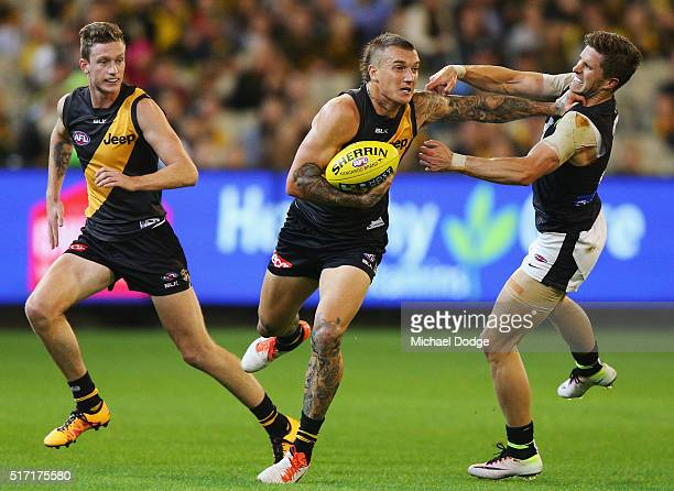Dustin Martin of the Tigers fends off Marc Murphy of the Blues during the round one AFL match between the Richmond Tigers and the Carlton Blues at...