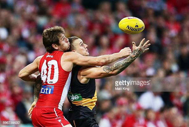 Dustin Martin of the Tigers is challenged by Nick Smith of the Swans during the round 23 AFL match between the Sydney Swans and the Richmond Tigers...