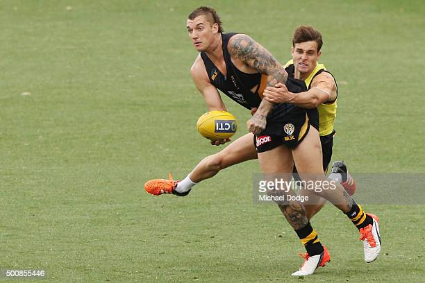 Dustin Martin of the Tigers is tackled by Anthony Miles during a Richmond Tigers AFL training session at Punt Road Oval on December 11 2015 in...