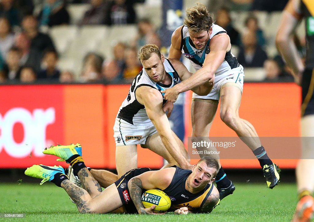 <a gi-track='captionPersonalityLinkClicked' href=/galleries/search?phrase=Dustin+Martin&family=editorial&specificpeople=5404528 ng-click='$event.stopPropagation()'>Dustin Martin</a> of the Tigers is tackled by Brad Ebert of the Power during the round six AFL match between the Richmond Tigers and the Port Adelaide Power at Melbourne Cricket Ground on April 30, 2016 in Melbourne, Australia.