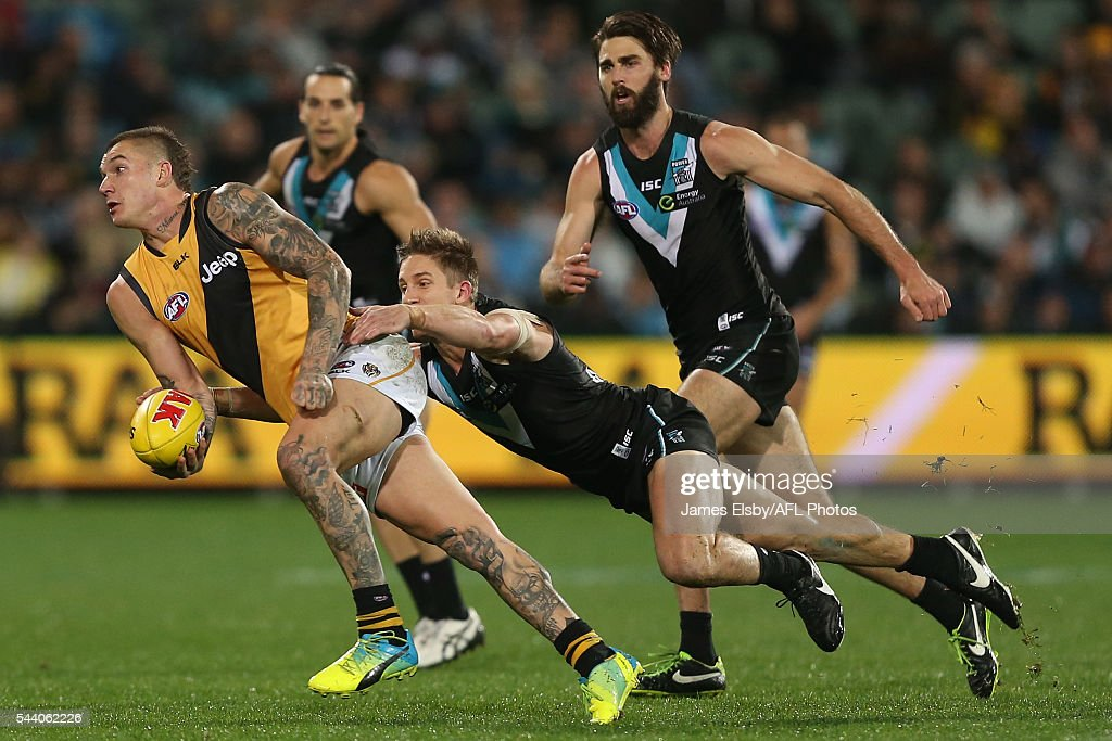Dustin Martin of the Tigers is tackled by Hamish Hartlett of the Power during the 2016 AFL Round 15 match between Port Adelaide Power and the Richmond Tigers at Adelaide Oval on July 1, 2016 in Adelaide, Australia.