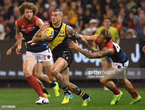 Dustin Martin of the Tigers is tackled by James Harmes of the Demons during the round five AFL match between the Richmond Tigers and the Melbourne...