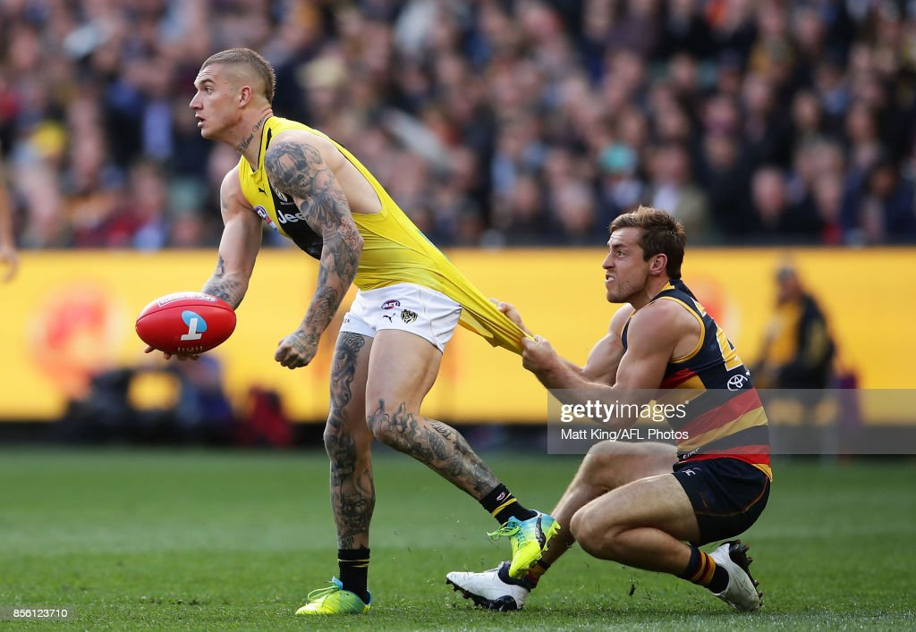 Dustin Martin of the Tigers is tackled by Richard Douglas of the Crows during the 2017 AFL Grand Final match between the Adelaide Crows and the Richmond Tigers at Melbourne Cricket Ground on September 30, 2017 in Melbourne, Australia.