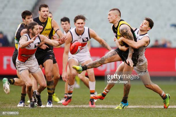 Dustin Martin of the Tigers kicks the ball away from Josh Kelly of the Giants during the round 18 AFL match between the Richmond Tigers and the...