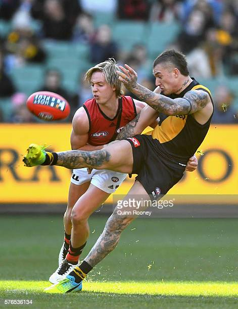 Dustin Martin of the Tigers kicks whilst being tackled by Darcy Parish of the Bombers during the round 17 AFL match between the Richmond Tigers and...