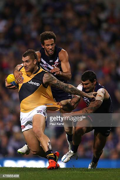Dustin Martin of the Tigers looks to break from a tackle by Zac Clarke and Clancee Pearce of the Dockers during the round 10 AFL match between the...