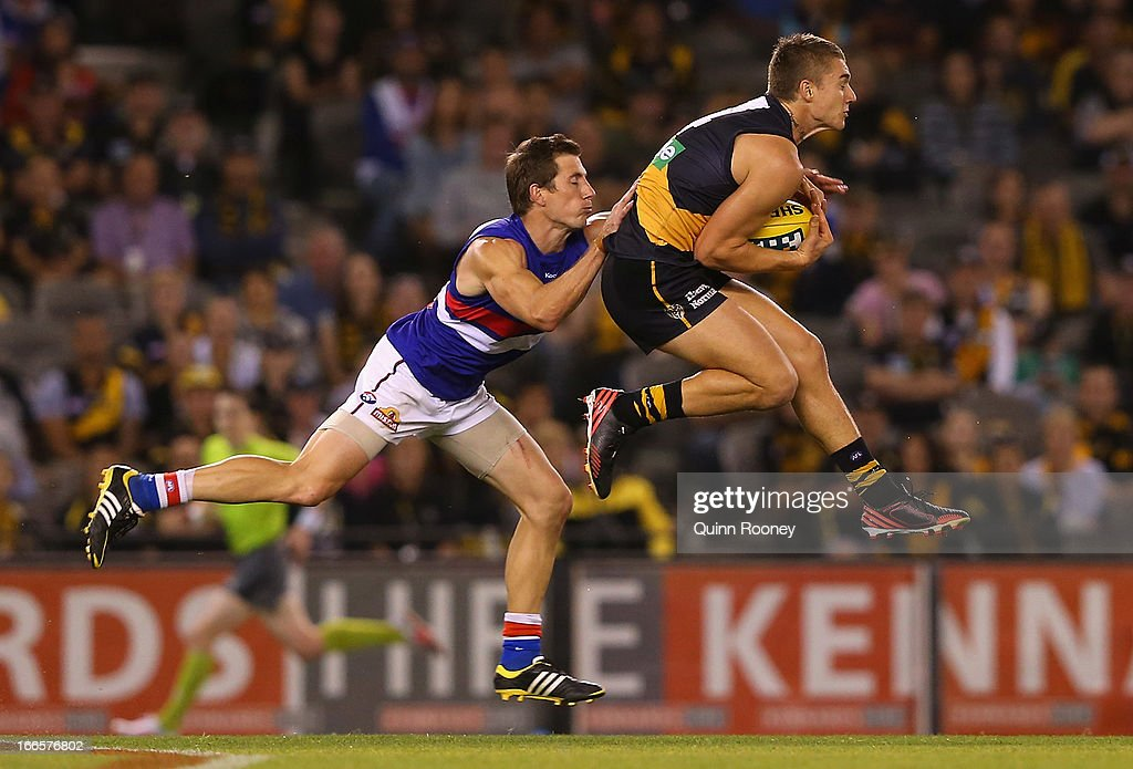 Dustin Martin of the Tigers marks infront of Dale Morris of the Bulldogs during the round three AFL match between the Richmond Tigers and the Western Bulldogs at Etihad Stadium on April 14, 2013 in Melbourne, Australia.