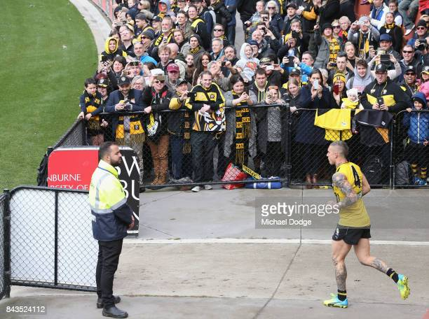 Dustin Martin of the Tigers runs out in front of fans during a Richmond Tigers AFL training session at Punt Road Oval on September 7 2017 in...