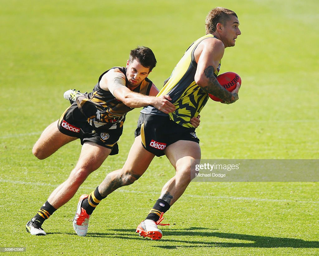 <a gi-track='captionPersonalityLinkClicked' href=/galleries/search?phrase=Dustin+Martin&family=editorial&specificpeople=5404528 ng-click='$event.stopPropagation()'>Dustin Martin</a> of the Tigers runs with the ball away from Corey Ellis of the Tigers during the Richmond Tigers AFL intra-club match at Punt Road Oval on February 12, 2016 in Melbourne, Australia.