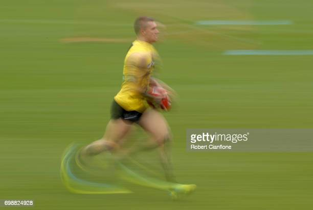 Dustin Martin of the Tigers runs with the ball during a Richmond Tigers AFL training session at Punt Road Oval on June 21 2017 in Melbourne Australia