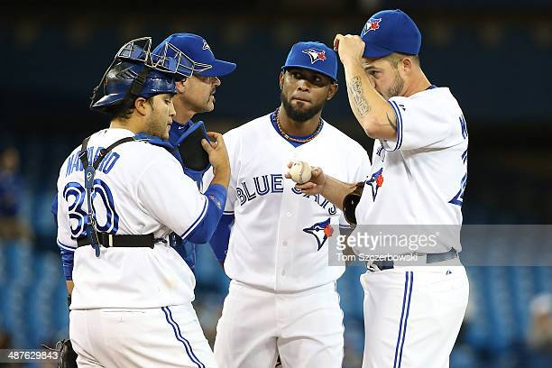 Dustin McGowan of the Toronto Blue Jays is visited on the mound by pitching coach Pete Walker in the fifth inning as Dioner Navarro and Jose Reyes...