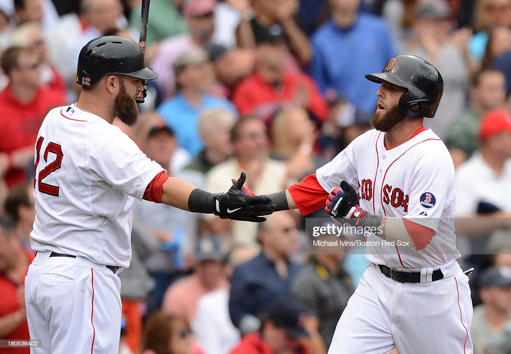 Dustin Pedroia 315 of the Boston Red Sox is congratulated by Mike Napoli #12 after scoring a run against the New York Yankees during the third inning on September 14, 2013 at Fenway Park in Boston Massachusetts.