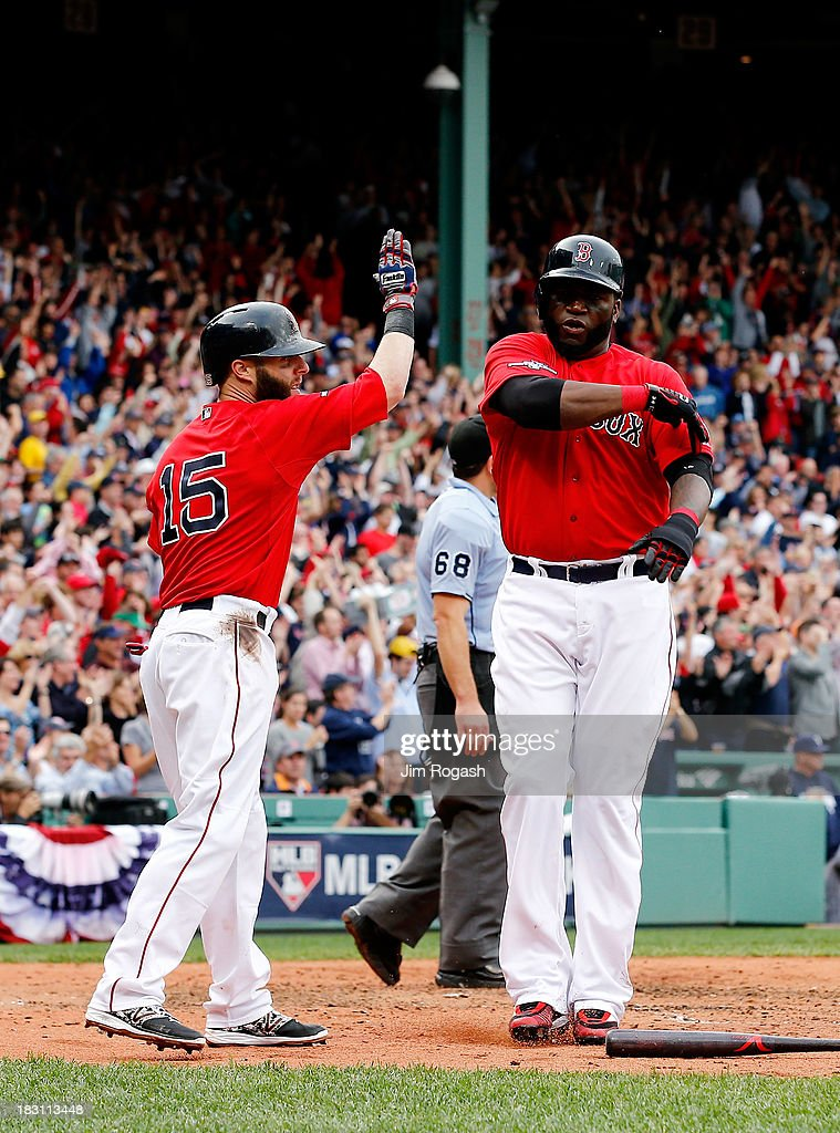 Dustin Pedroia #15 and David Ortiz #34 of the Boston Red Sox celebrate after scoring on a double by Jonny Gomes #5 against the Tampa Bay Rays in the fourth inning during Game One of the American League Division Series at Fenway Park on October 4, 2013 in Boston, Massachusetts.